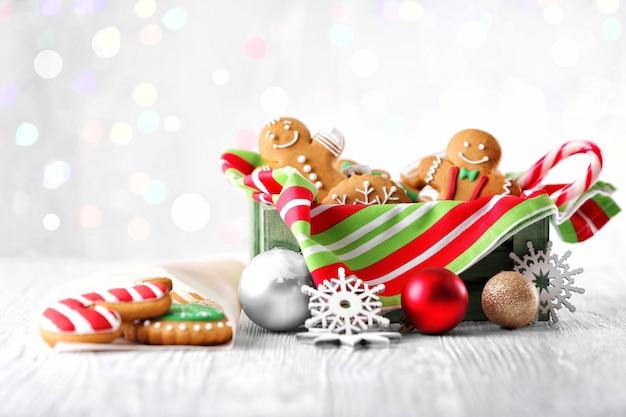 Scatola con biscotti gustosi e decorazioni natalizie su tavolo in legno chiaro