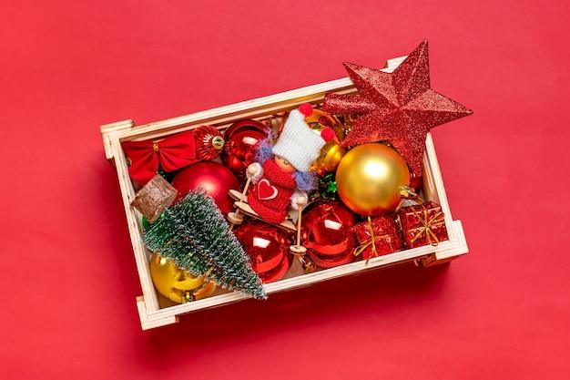 Scatola con giocattoli - arco, palla, stella, nastro, confezione regalo, albero di natale isolato su sfondo rosso