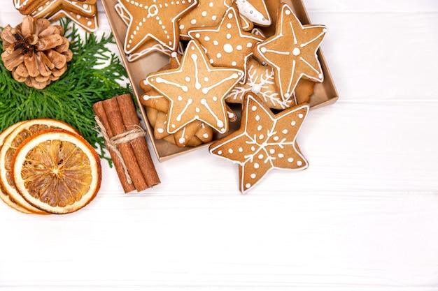 Scatola con una varietà di biscotti di panpepato di natale, albero di natale su sfondo bianco. cottura natalizia