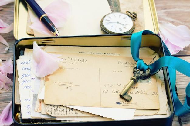 Scatola con posta vintage e orologio antico