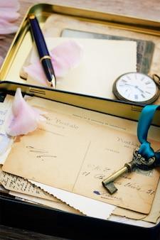 Scatola con posta vintage, chiave e orologio antico da vicino