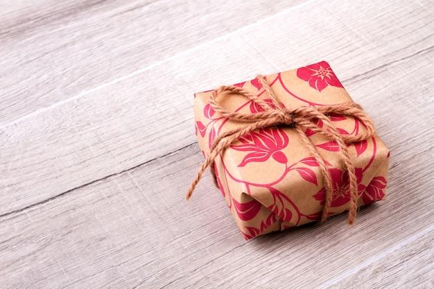 Scatola in involucro con corda. regalo sdraiato su una superficie di legno. tradizione di inviare regali. simpatico regalo per un amico.