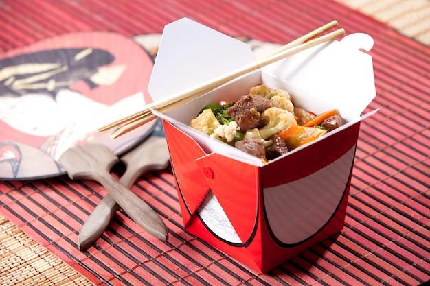 Scatola di yakisoba con hashi accanto a ventaglio giapponese