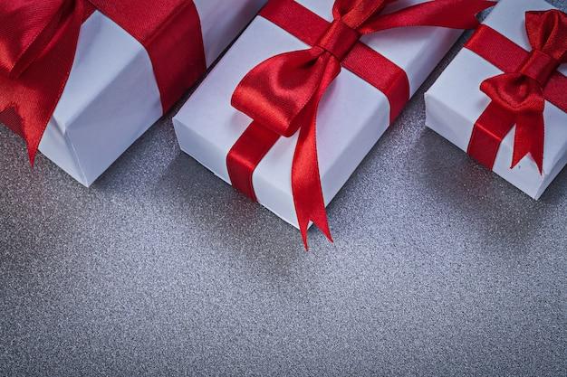 Regali in scatola con nastri rossi legati sulla superficie grigia direttamente sopra il concetto di vacanze