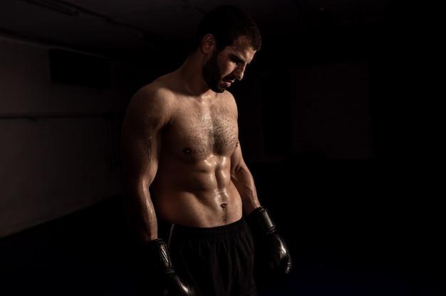 Boxer in guantoni da boxe in posa dopo l'allenamento.