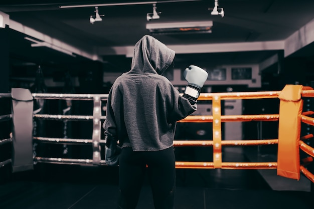 Ragazza del pugile con felpa con cappuccio e guantoni da boxe in piedi sul ring con le spalle girate. una mano alzata.