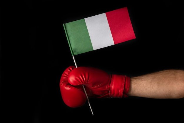 La mano del pugile tiene la bandiera dell'italia. guantoni da boxe con bandiera italiana. sfondo nero.