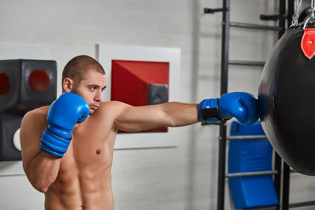 Uomo pugile durante la boxe che colpisce il sacco pesante in palestra di formazione fitness. torso nudo