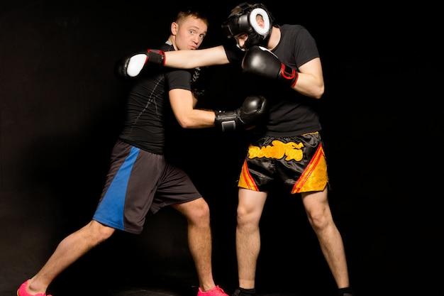 Il pugile calcola male e manca il suo pugno mentre il suo avversario guarda il suo pugno guantato sfrecciargli sopra la testa durante un combattimento