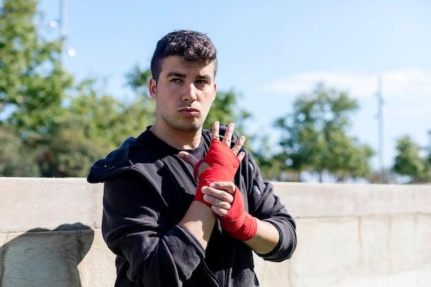 Boxer preparando per l'allenamento con la fasciatura dell'avambraccio all'aperto
