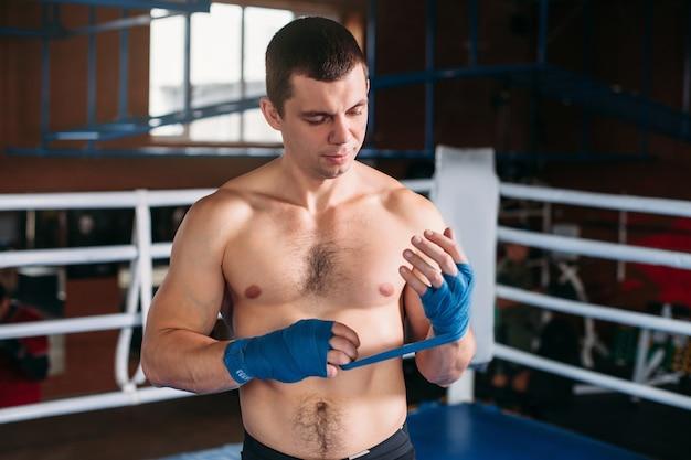 Il pugile tira la benda prima del combattimento o dell'allenamento.
