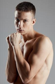 Boxer con muscoli del braccio gonfiati bicipiti sport fitness muro grigio vista ritagliata.