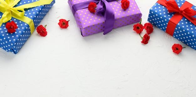 Le scatole sono confezionate in carta natalizia con pois e legate con un nastro di seta su uno sfondo, regalo di compleanno, sorpresa, spazio per le copie