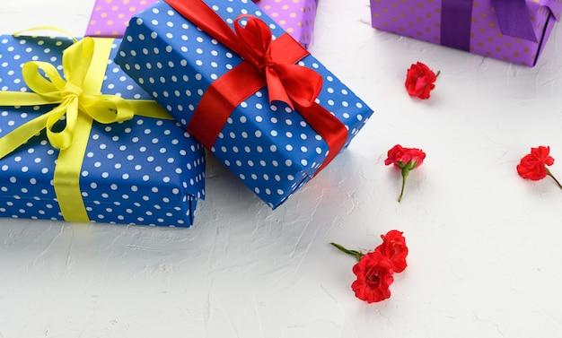 Le scatole sono confezionate in carta per le vacanze con pois e legate con un nastro di seta su uno sfondo, regalo di compleanno, sorpresa