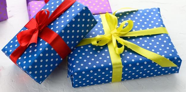 Scatole confezionate in carta blu festiva e legate con nastro di seta su sfondo bianco, regalo di compleanno, sorpresa, primo piano