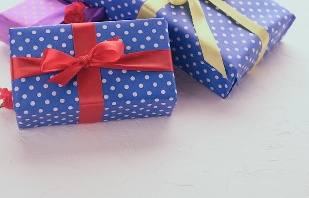 Scatole confezionate in carta blu festiva e legate con nastro di seta su sfondo bianco, regalo di compleanno, sorpresa