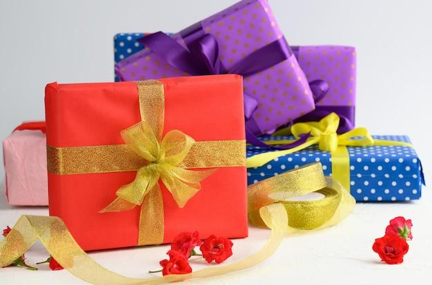 Scatole confezionate in carta festiva e legate con nastro di seta su sfondo bianco, regalo di compleanno, sorpresa