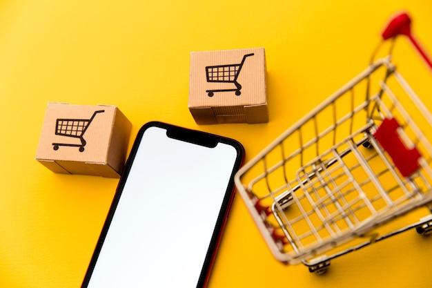 Scatole in un carrello della spesa o in un carrello e smartphone mobile