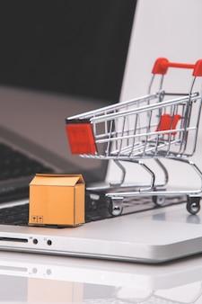 Scatole e trolley su un laptop lo shopping online è una forma di commercio elettronico che consente ai consumatori di acquistare direttamente le merci da un venditore