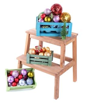 Scatole con decorazioni natalizie su scaletta, isolate su bianco