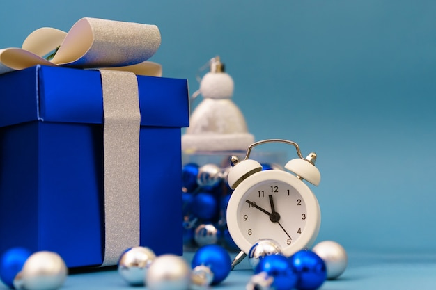 Scatole con regali e giocattoli dell'albero di natale blu con orologio, concetto di tempo di vacanze di natale