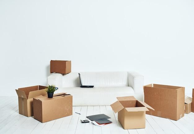 Scatole con cose divano bianco disimballaggio ufficio in movimento