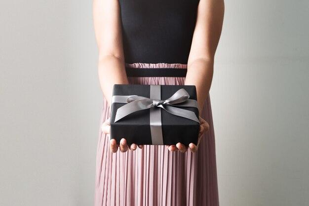 Vendita di santo stefano, giovane donna in possesso di un'offerta di confezione regalo al destinatario