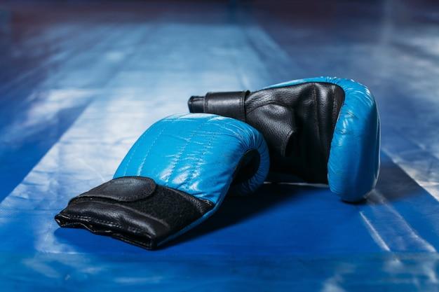 Guantoni da boxe sul pavimento del ring.