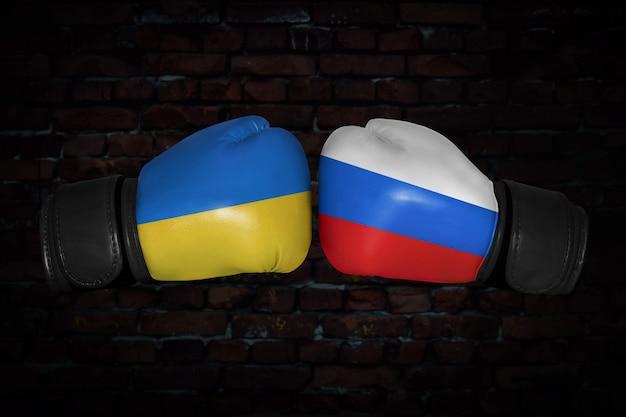 Incontro di boxe. confronto tra ucraina e russia. bandiere nazionali russe e ucraine sui guantoni da boxe. competizione sportiva tra i due paesi. concetto del conflitto di politica estera.