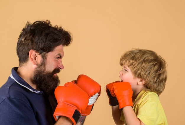 Addestramento di boxe ragazzo in guantoni da boxe che si allena con il suo allenatore pugilato sul ring che perfora l'infanzia a eliminazione diretta
