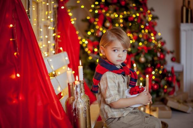 Ragazzo 4-6 anni in una sala festiva rossa e una bella acconciatura alla vigilia di capodanno
