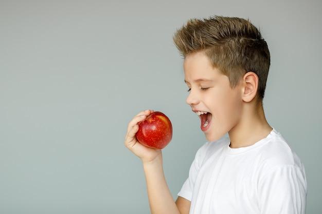 Ragazzo che sta per mordere una mela rossa, tenendo un frutto con una mano