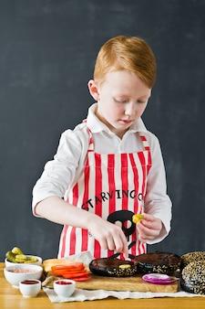 Un ragazzo in un grembiule che cucina in cucina burger.