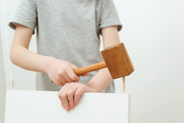Il ragazzo assembla uno scaffale per libri da solo. papà e figlio piccolo che montano mobili a casa.