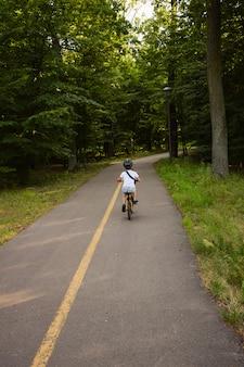 Un ragazzo in bicicletta e con indosso un casco corre da solo su un sentiero asfaltato nel parco