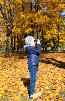 Un ragazzo con una giacca blu scatta foto delle caratteristiche della stagione autunnale dell'anno, vista laterale