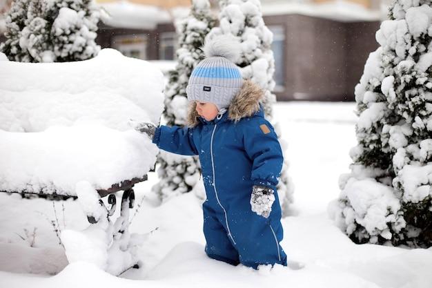 Un ragazzo con una tuta blu e un cappello vede la neve per la prima volta e si trova vicino a una panchina sullo sfondo di un albero di natale coperto di neve nel parco.