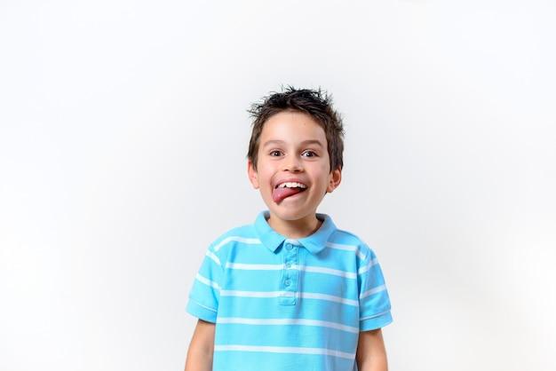 Il ragazzo con una maglietta blu mostra la sua lingua e guarda la telecamera.