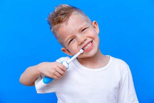 Ragazzo lavarsi i denti con spazzolino elettrico su blu