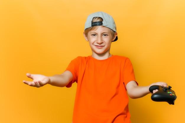 Un ragazzo con un berretto e una maglietta arancione allarga le mani in direzioni diverse tiene un gamepad in una mano