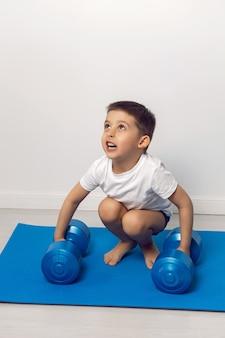 Un bambino di quattro anni solleva i manubri di cinque chilogrammi in una stanza bianca in piedi