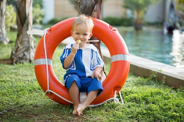 Bambino del ragazzo che gioca con il salvagente. cura del bambino e concetto di infanzia.