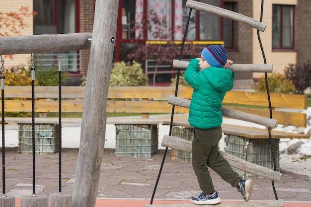 Ragazzo sale una scala di corda nel parco