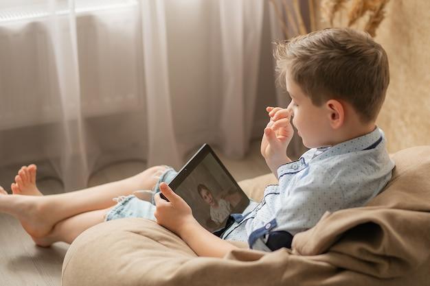 Il ragazzo comunica online con la sua ragazza, la ragazza sullo schermo del tablet sorride e ascolta attentamente la storia di un amico online