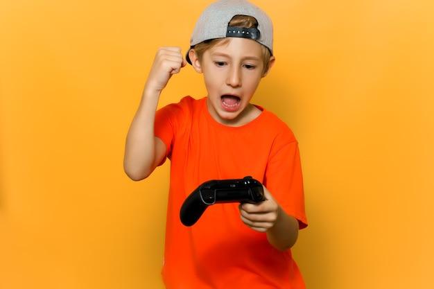 Il ragazzo giocatore di computer si rallegra della vittoria tenendo in mano un joystick e sollevandoli
