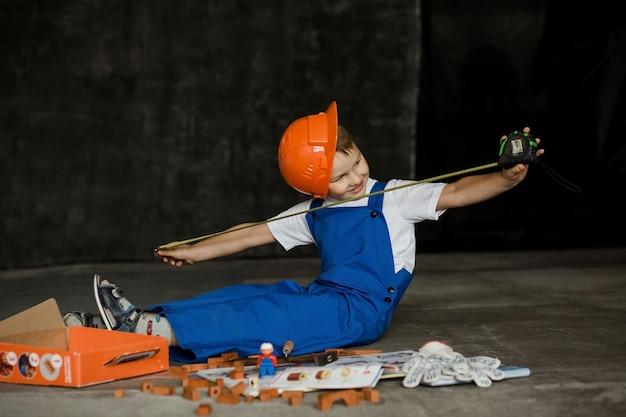 Ragazzo in un casco e una tuta da costruzione. futuro costruttore.