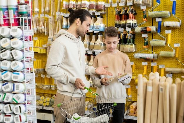 Ragazzo che si consulta con il padre per un nuovo pennello in un supermercato di ferramenta