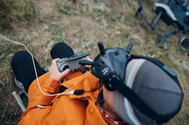 Ragazzo che controlla drone quadricottero fpv per fotografia aerea e videografia con telecomando per antenna per occhiali.