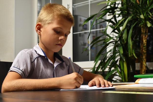Il ragazzo fa i compiti la sera. carico scolastico sui bambini.