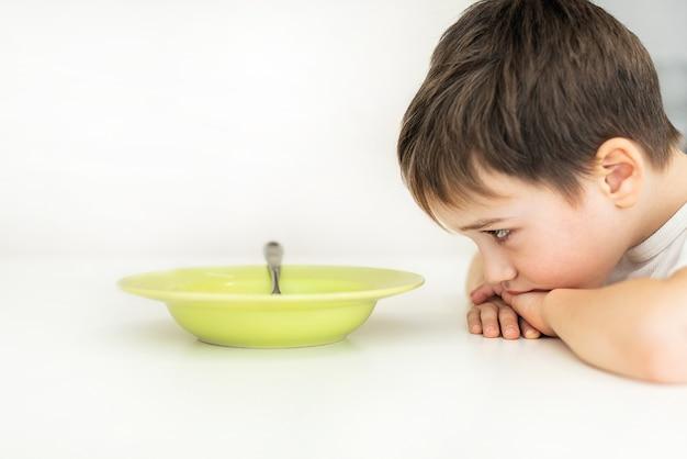 Il ragazzo non vuole mangiare si siede a un tavolo, davanti a lui c'è un piatto di zuppa